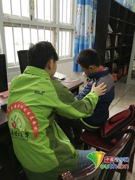 在微笑小屋里,武汉理工研支团志愿者李泽民引导学生拨打亲情电话。武汉理工支教团 供图
