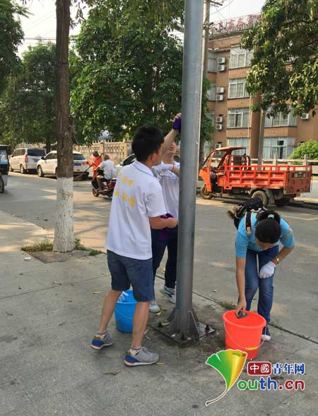 田东县志愿者清理路边小广告美化县城大环境