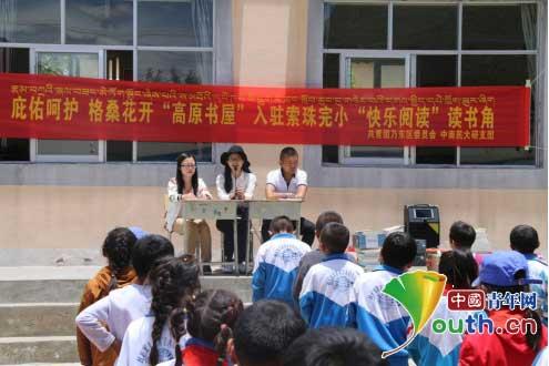 中南民族大学研究生支教团队员侯凤超在和索珠完小的孩子们分享读书