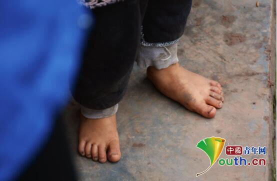 图为哈工大研支团成员在家访中看到光着脚的留守儿童。赵玺 供图