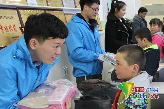 图为吉林大学研支团团长高天宇为结对孩子送上学习用品。高天宇 供图