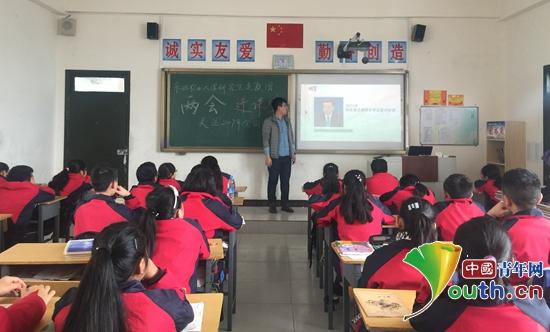 """东北农业大学研支团让""""两会""""走进课堂.图为研支团成员为学生讲解图片"""