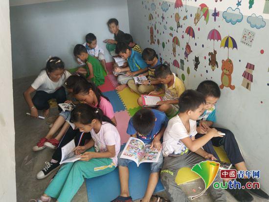 图为田东县祥周镇布兵村布兵小学学生在图书角看书.