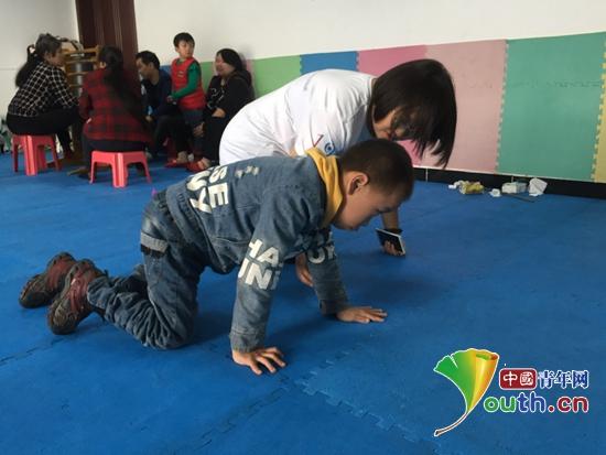 重庆医科大学研支团成员陪伴孩子爬行进行交流。熊林 供图