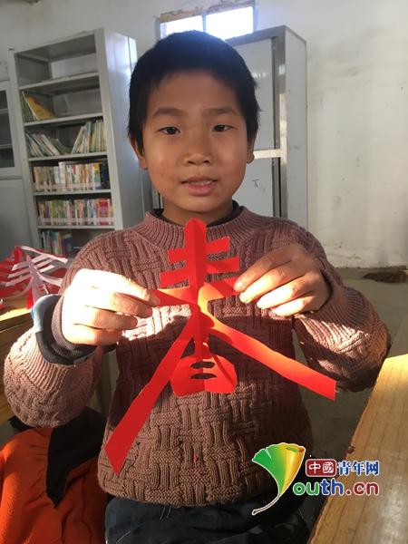 张一串串剪纸作品——千纸鹤像是飞扬的火苗,妆点了石桥教学点的教室