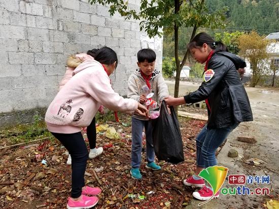 公安大学/图为护绿小使者们正在将捡拾的垃圾装入塑料袋中。公安大学研支...