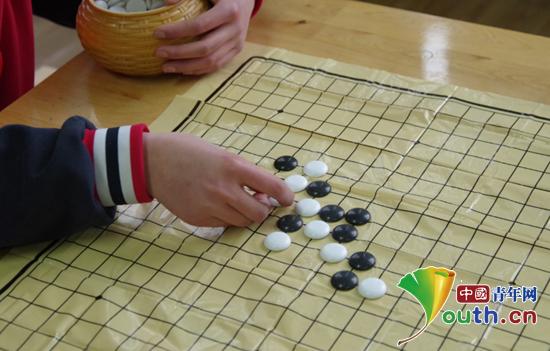 图为参加五子棋比赛的选手正举棋落子。上海财经大学研支团 供图