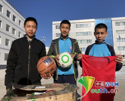 中国人民大学研支团向塔城市第四中学捐赠体育器材。图为塔城市第四中学学生展示获赠的体育物资。