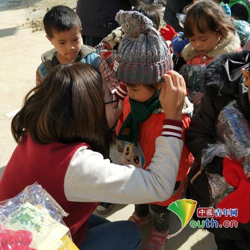 江西师范大学研支团成员为望谟县的孩子戴上帽子和围巾。黄俊宇 供图