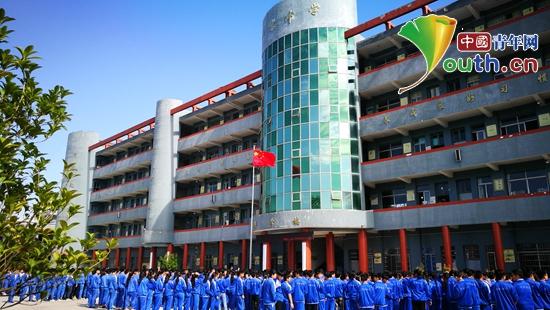 贵州大学研支团在丹寨县兴仁中学组织开展系列活动迎接祖国生日的到来。图为兴仁中学学生与国旗合影。