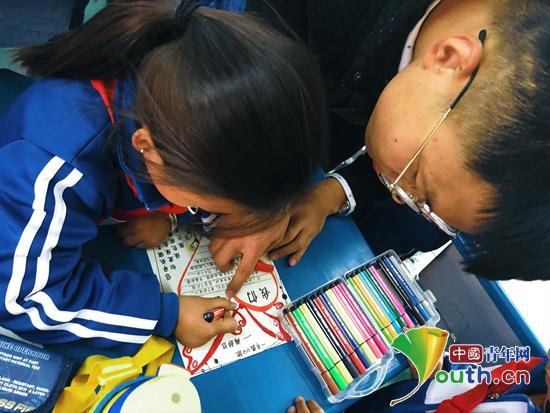 图为陕西科技大学第二十届研究生支教团队员赵炳达指导孩子绘制手抄报