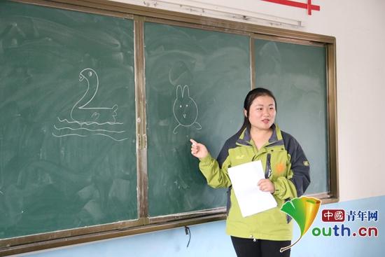 图为志愿者季婷婷为二年级学生上简笔画课.