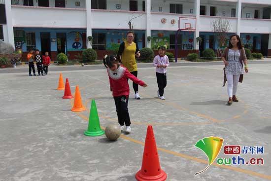 图为武关驿镇中心小学趣味足球联赛参赛选手表演带球绕桩.