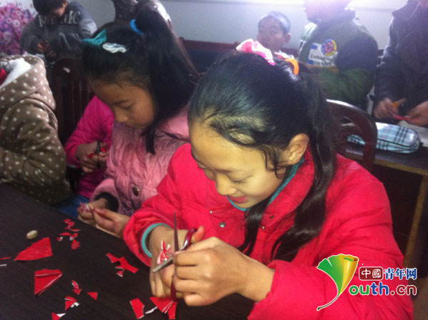 学生在跟着老师学习剪窗花