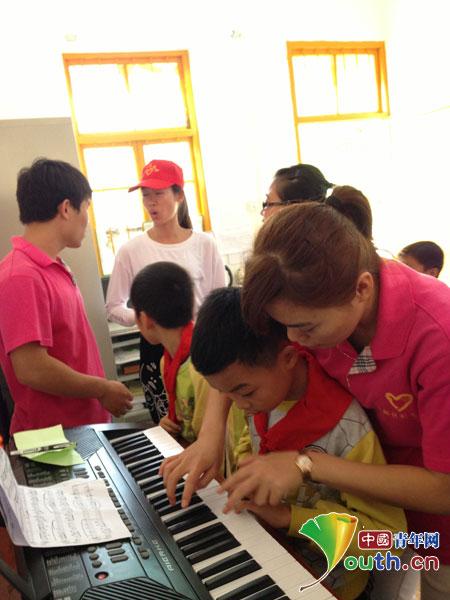 志愿者正在教孩子弹电子琴-七彩小屋揭牌