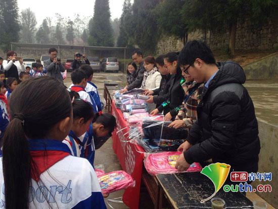 华北水利水电大学研究生支教团队员为洒雨镇民族小学留守儿童发放爱