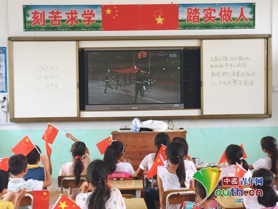 孩子们观看爱国主义动画视频《那年那兔那些事儿》。广西大学研支团 供图