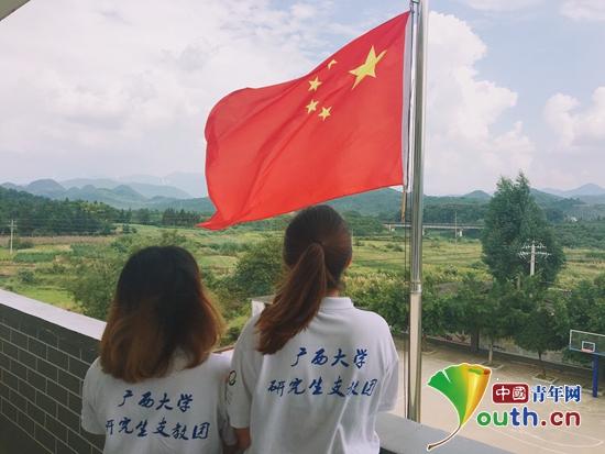 广西大学研支团成员面向国旗合唱歌曲《歌唱祖国》。广西大学研支团 供图