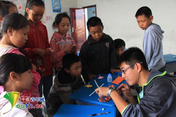 中国青年网北京10月31日电(记者李彦龙)近日,山东师范大学第十五届研究生支教团赴重庆荣昌安北小学开展七彩课堂折纸艺术活动,增强了孩子们的动手能力,丰富了孩子们的课余生活。  支教团成员在教孩子制作折纸作品   安北小学是位于荣昌县安富街道的一所村小,设有一至六年级,共有学生八十余名。支教团成员进入三至六年级课堂,为孩子们带来了一堂生动的折纸课。课堂中,支教团成员悉心地辅导孩子们折出桃心、星星、电话、狐狸等造型,孩子们拿着手中的彩纸认真地跟随着支教团成员,一步步折出自己喜爱的作品。在制作的过程中