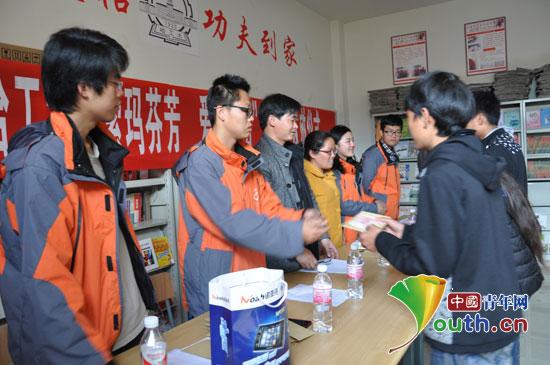 团宁蒗县委领导与哈尔滨工业大学支教队员一起给学生代表发放资助。