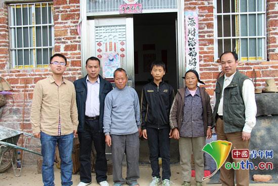 广西大学支教团走访受助留守儿童并与其家人一起合影。