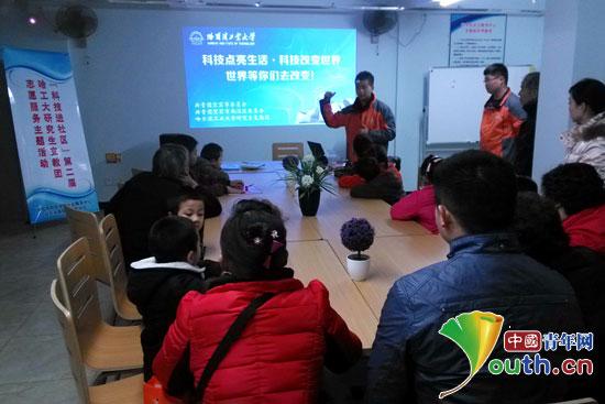 哈工大支教团赵玉林借助幻灯片为社区孩子们展示哈工大近年来在机器人科学方面的研究现状。