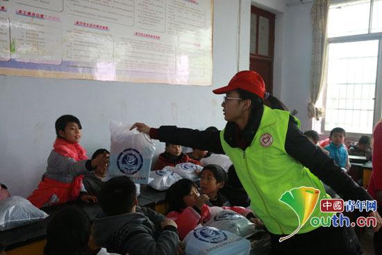大连海事大学研究生支教团成员给孩子发放爱心礼包.