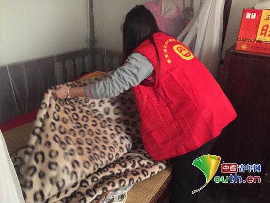 南京师范大学研支团到绵竹市滨河社区民生公寓看望抗美援朝老兵沈刚云。图为志愿者为老人整理床铺。