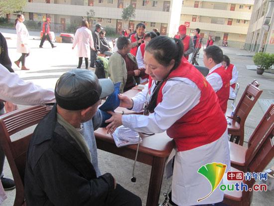 """""""关爱老人,你我同行""""志愿服务活动.图为志愿者为老人进行义诊图片"""