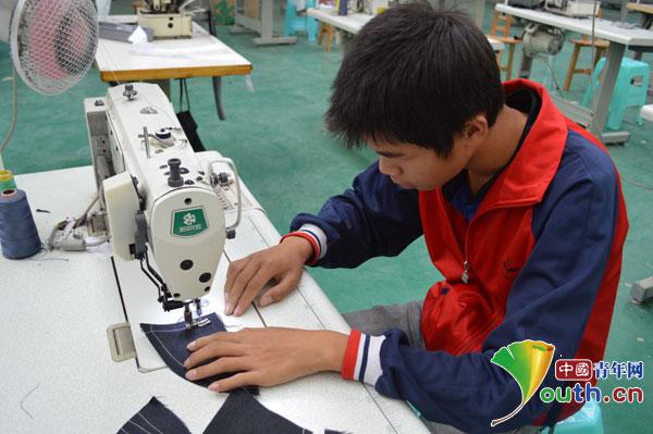 特教学生在认真操作缝纫机